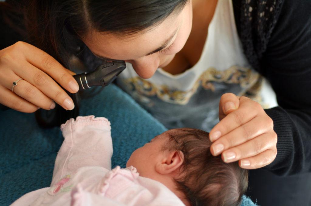 Ärztin bei der Augenuntersuchung eines Säuglings